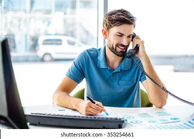 Photo of young, handsome, successful and confident businessman. Young businessman working with computer and talking on phone. White modern office interior