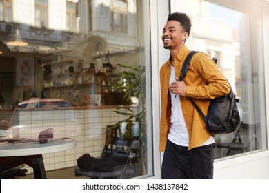 Photo of young happy African American man in yellow shirt walking down the street listening favorite song on headphones, looks cheerful, enjoy the sunny day in the city and broadly smiling.