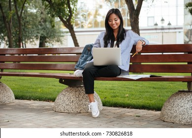 Photo of young happy asian female student relaxing with laptop, sitting on wooden bench in park