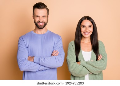 Photo of young happy cheerful smiling positive couple wife husband with crossed hands isolated on beige color background