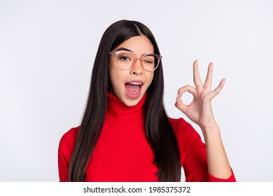 Photo of young happy excited funky charming asian girl show okay sign winking eye isolated on grey color background