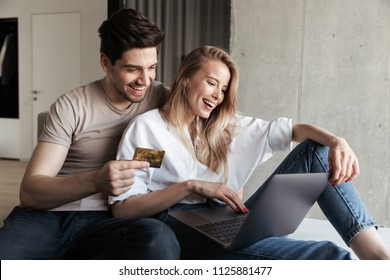 Photo of young happy loving couple in home indoors on sofa using laptop computer holding credit card.