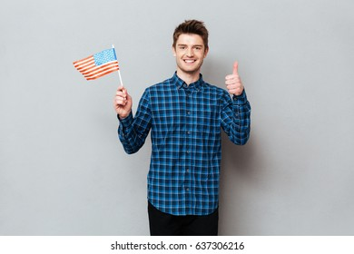 Photo of young happy man standing over grey wall and looking at camera while showing thumbs up and holding USA flag.