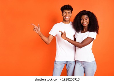 Photo of young happy positive afro couple hug each other point finger copyspace advertisement isolated on orange color background