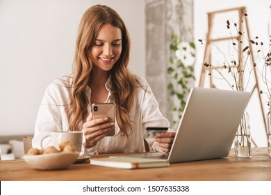 Photo of young happy redhead business woman sit indoors in office using laptop computer and mobile phone holding credit card.