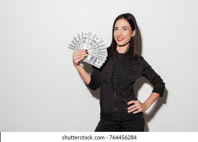 Photo of young happy woman with red lips standing isolated over white wall. Looking camera holding money.