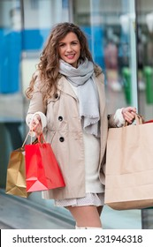 Photo of young joyful woman with shopping bags on the background of shop windows. Outdoors.