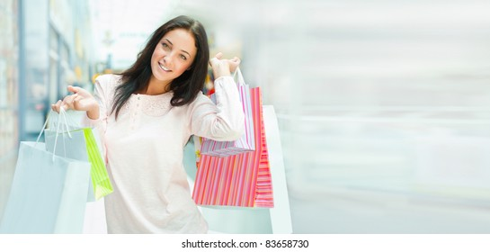 Photo of young joyful woman with shopping bags on the background of shop windows at mall. She is smiling and walking. Lots of Copyspace