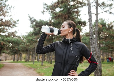 Photo of young lady runner in warm clothes and headphones standing in autumn park while drinking water