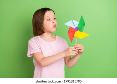 Photo of young little girl blow windmill pinwheel rotate toy isolated over green color background