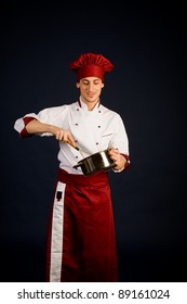 photo of young male chef with a pot in his hand who is cooking