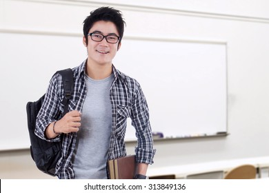 Photo of young male student standing the classroom while smiling at the camera