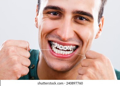 Photo of young man with braces using dental floss,Dental hygiene