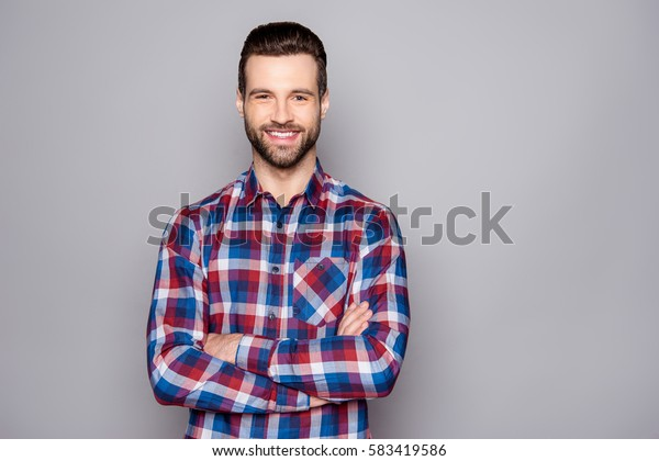 A photo of young man in checkered shirt with beaming smile posing against gray background
