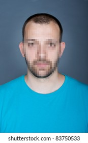 Photo of a young man, with hidden face via pixelation method. Large square pixels viewed at 100%. Identity concept.