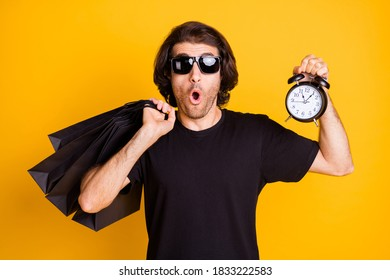 Photo of young man hold store bags timepiece clock open mouth wear black t-shirt sunglass isolated yellow color background