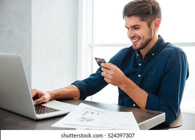 Photo of young man holding a credit card and typing. Online shopping on the internet using a laptop. Looking at the laptop.