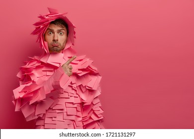 Photo of young man points right displeased, demonstrates bad result to coworkers, purses lips, wears funny paper outfit made of stickers, doesnt like something, shows copy space on pink background