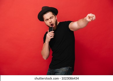 Photo of young man wearing black t-shirt and hat singing while listening to music using cell phone and wireless earphones isolated over red wall