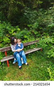 Photo of a young mother and her son sitting on a park bench surrounded by trees and bushes.
