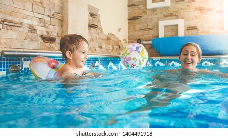 Photo of young mother teaching swimming her little 3 years old boy child and playing with colorful beach ball at indoor swimming pool