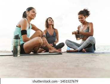 Photo of young multiethnic sportswomen in tracksuits smiling and talking while sitting on yoga mats by seaside in morning