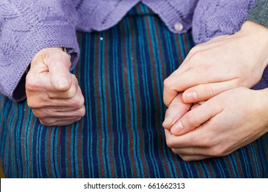Photo of young nurse holding elderly woman's hand