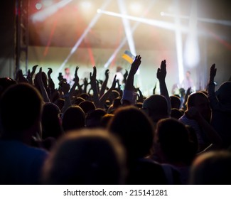 Photo of young peofans applauding to famous music band, nightlife, DJ on the stage in the club, crowd dancing on dance-floor, night performanceple having fun at rock concert,