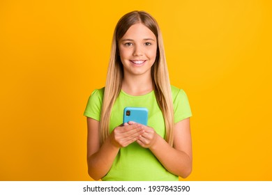 Photo of young preteen girl happy positive smile use smartphone chat type sms isolated over yellow color background