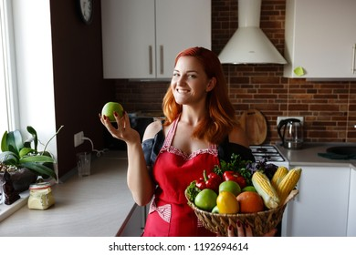 Photo of young pretty lady standing in kitchen while cooking fish. Woman preparing healthy meal in her rustic eco kitchen