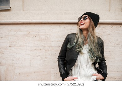 Photo of young pretty lady wearing hat and sunglasses walking on the street.