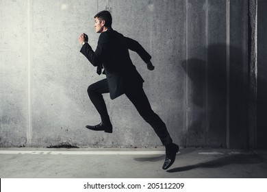 Photo of a young professional running against a concrete background
