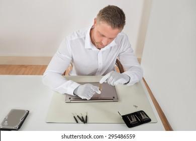 Photo Of Young Repairman Repairing Laptop At Desk