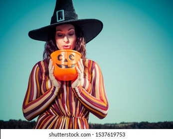 Photo of a young sexy woman holding a pumpkin candy bucket and looking inside and wearing a witch hat for Halloween theme.