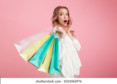Photo of young shocked woman standing isolated over pink background. Looking aside holding shopping bags.