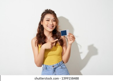 Photo of young smiling asian woman holding card
