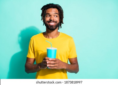 Photo of young smiling cheerful positive dreamy handsome african man hold cup of fizzy drink isolated on teal color background