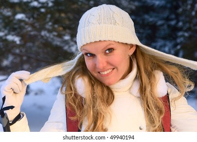 Photo of a young smiling girl in a knitted hat in winter.