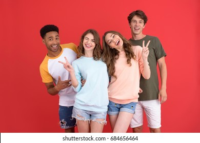 Photo of young smiling group of friends standing isolated over red background. Looking at camera showing peace gesture.