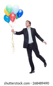 Photo of young smiling handsome man. Man holding a lot of colourful balloons and standing on white background. Concept for happy birthday