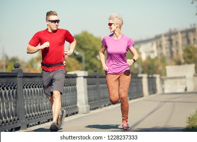 Photo of young sport couple running along promenade