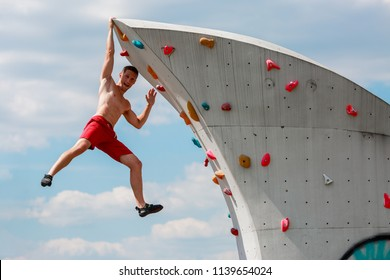Photo of young sporty guy in red shorts hanging on wall for rock climbing against blue sky with clouds