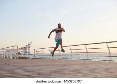 Photo of young sporty handsome bearded running guy doing morning exercises by the sea, warm-up before run, leads healthy active lifestyle. Fitness and sport concept.