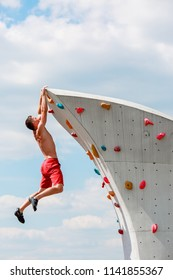Photo of young sporty man in red shorts hanging on wall for climbing against blue sky with clouds