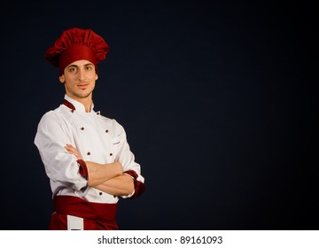 photo of young successful chef in front of a blue background