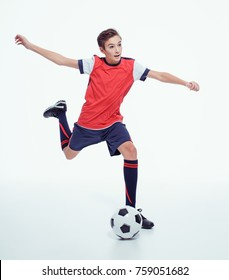 photo young teen boy with soccer ball doing flying kick, studio