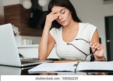 Photo of young tired woman analyzing home finances with laptop while suffering eyestrain and holding glasses.