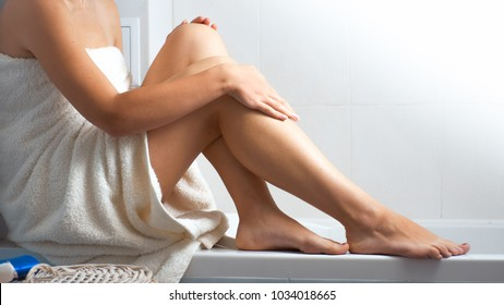 Photo of young woman in bath towel massaging her legs and feet