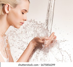 Photo of  young woman with clean skin and splash of water. Blonde woman with drops of water near her face. Spa treatment. Girl washing hands with water. Water and body.