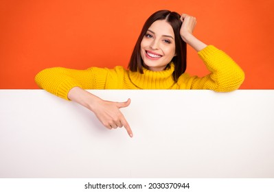 Photo of young woman happy positive smile point finger empty space poster ad promo choose isolated over orange color background